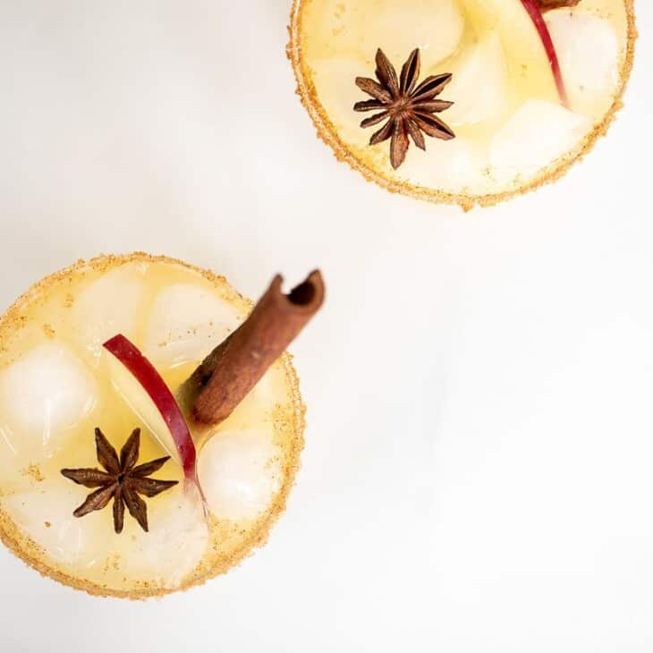 Clear glasses with apple cider margaritas, rimmed in sugar and garnished with a cinnamon stick on a marble surface.
