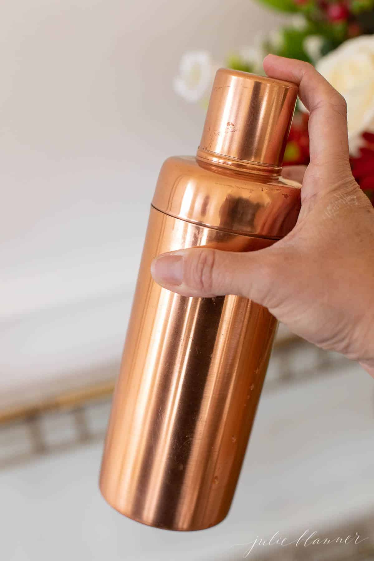 A hand holding a copper cocktail shaker.