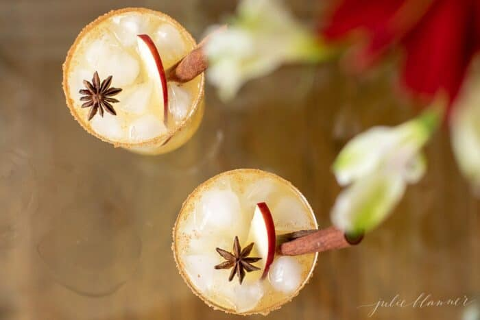 Clear glasses with apple cider margaritas, rimmed in sugar and garnished with a cinnamon stick on a wood surface.