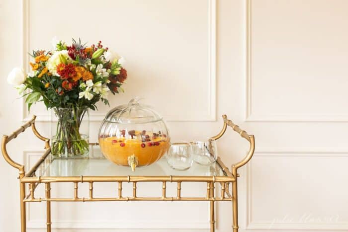 A glass bar cart with fall flowers in a vase, and a pumpkin drink dispenser filled with apple cider sangria.