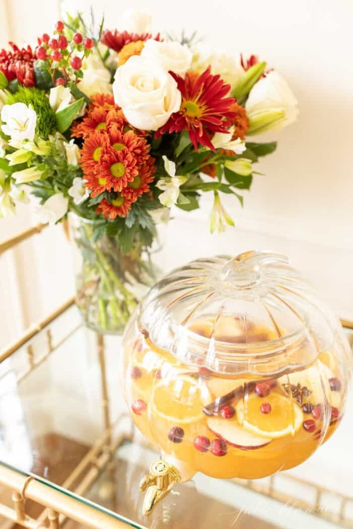 A clear glass pumpkin drink dispenser filled with apple cider sangria, flowers in the background.