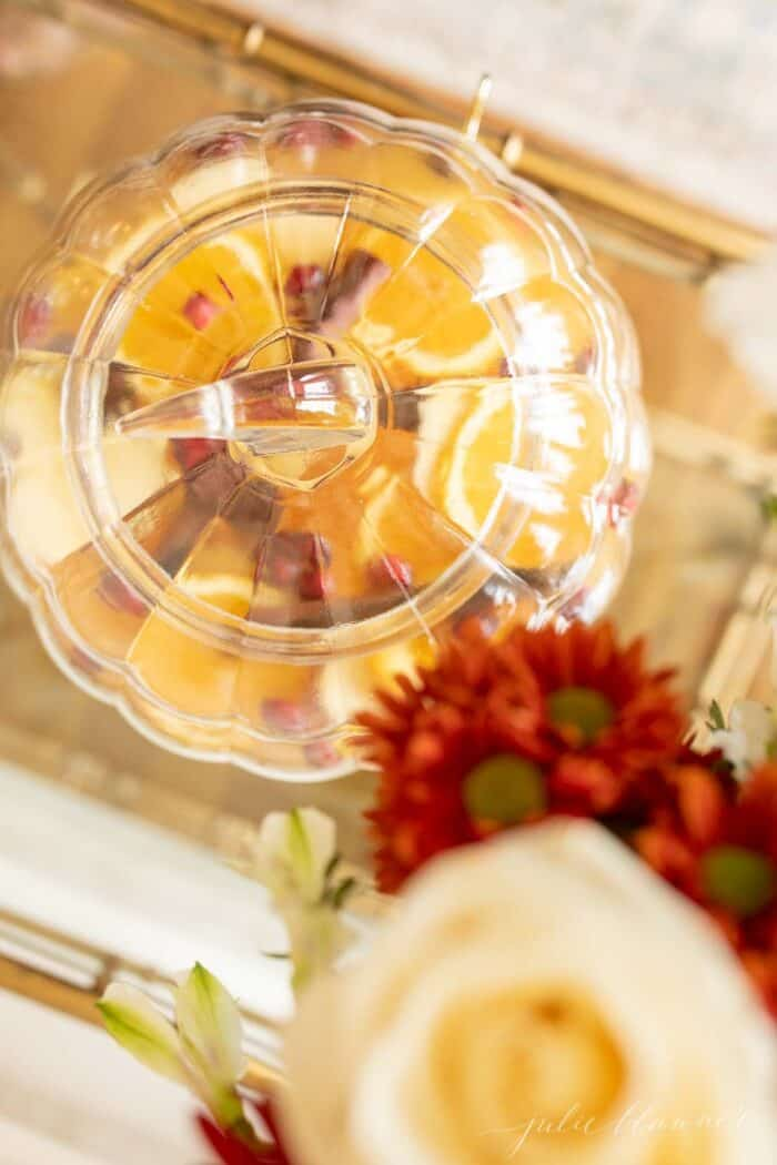 A clear glass pumpkin drink dispenser filled with apple cider sangria.