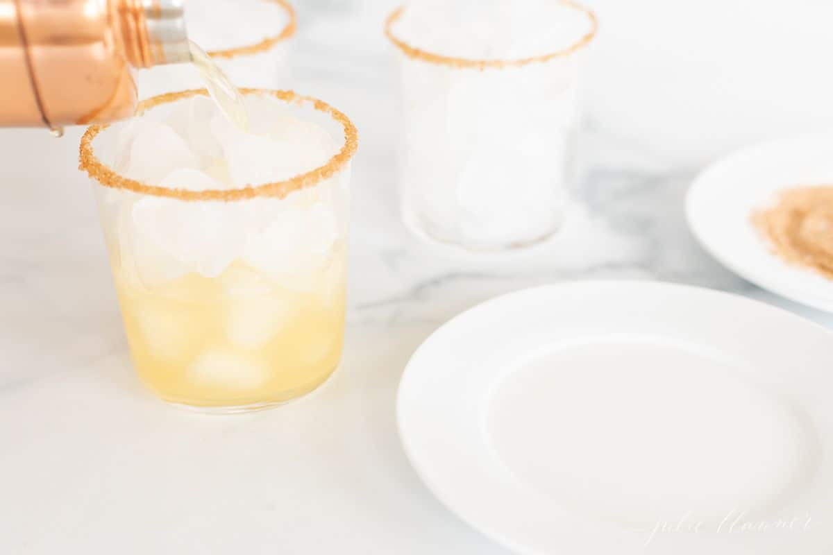 Three cocktail glasses with ice, a hand pouring an apple margarita into one from a copper mixer.