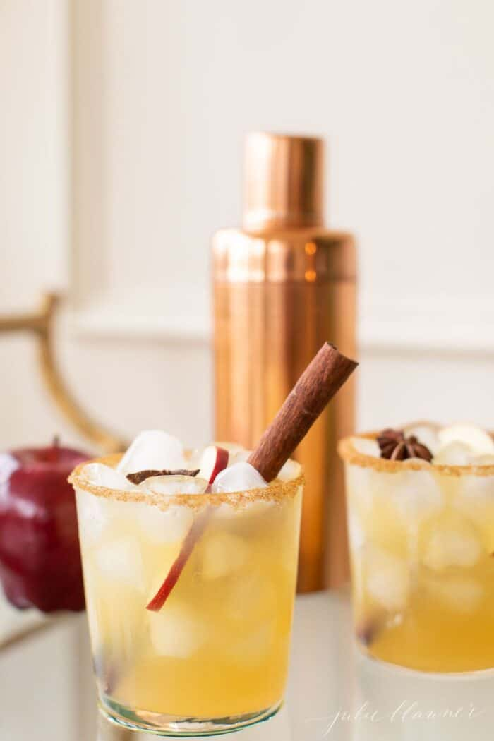 A copper cocktail shaker with clear glasses full of apple margaritas, cinnamon stick for garnish.