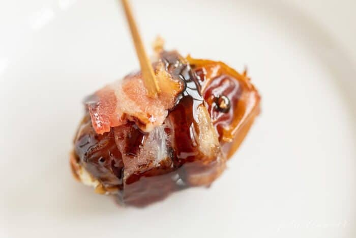 A date wrapped in bacon with a toothpick on a white surface.