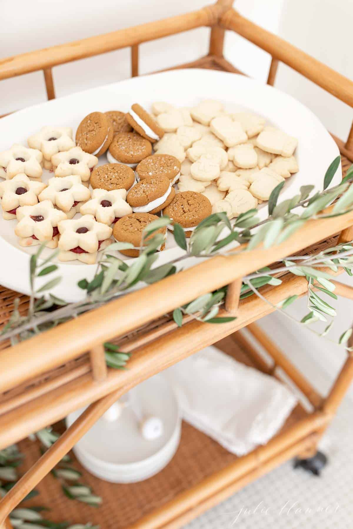 A bamboo bar cart with a white oval platter filled with Scandinavian Christmas cookies, fresh greenery accents.