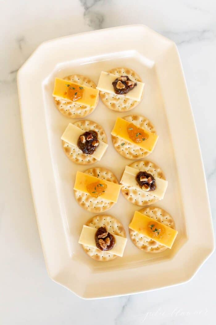 A display of individual cheese and crackers topped with jam on a white platter.