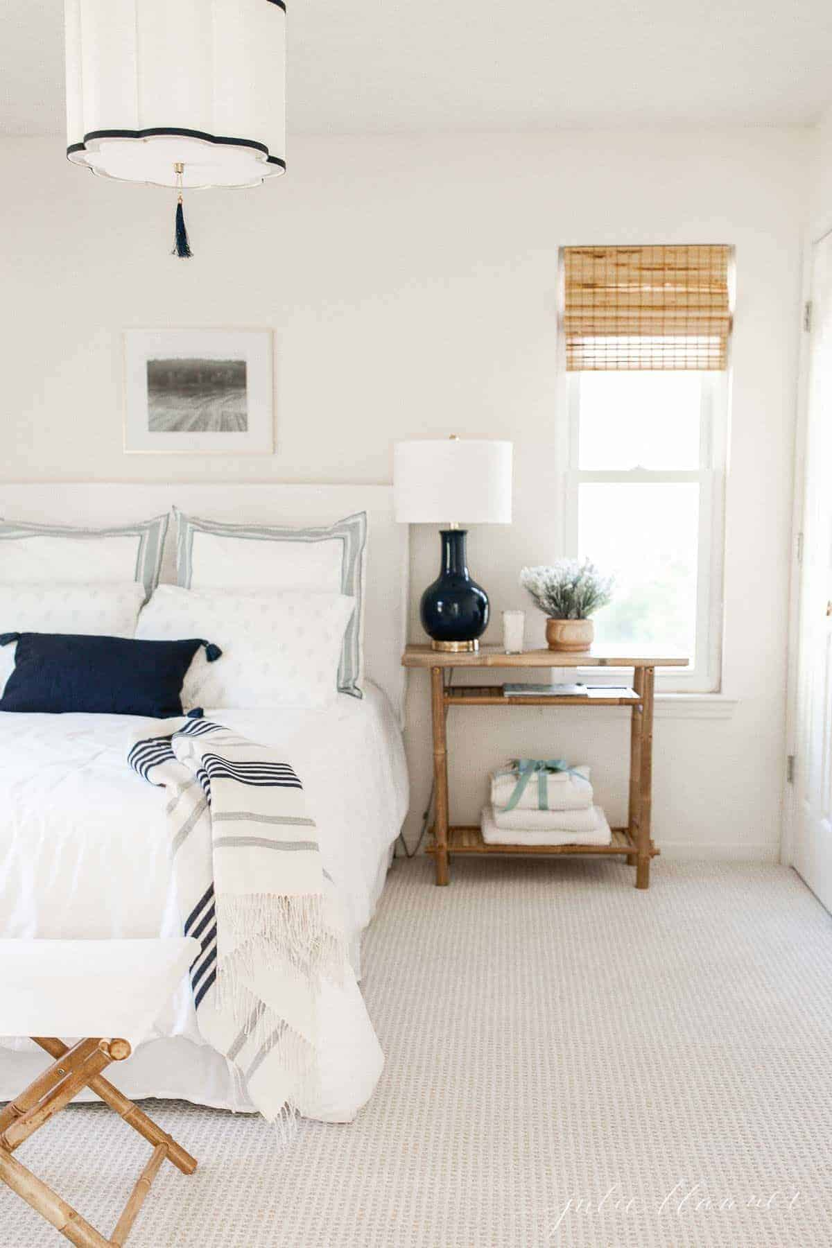 A white guest room with blue accents.