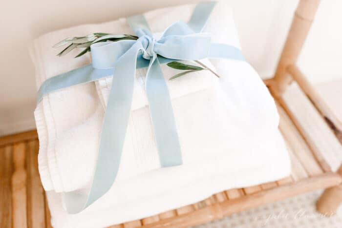 White towels in a guest room, tied in a blue velvet bow for a Scandinavian Christmas touch.