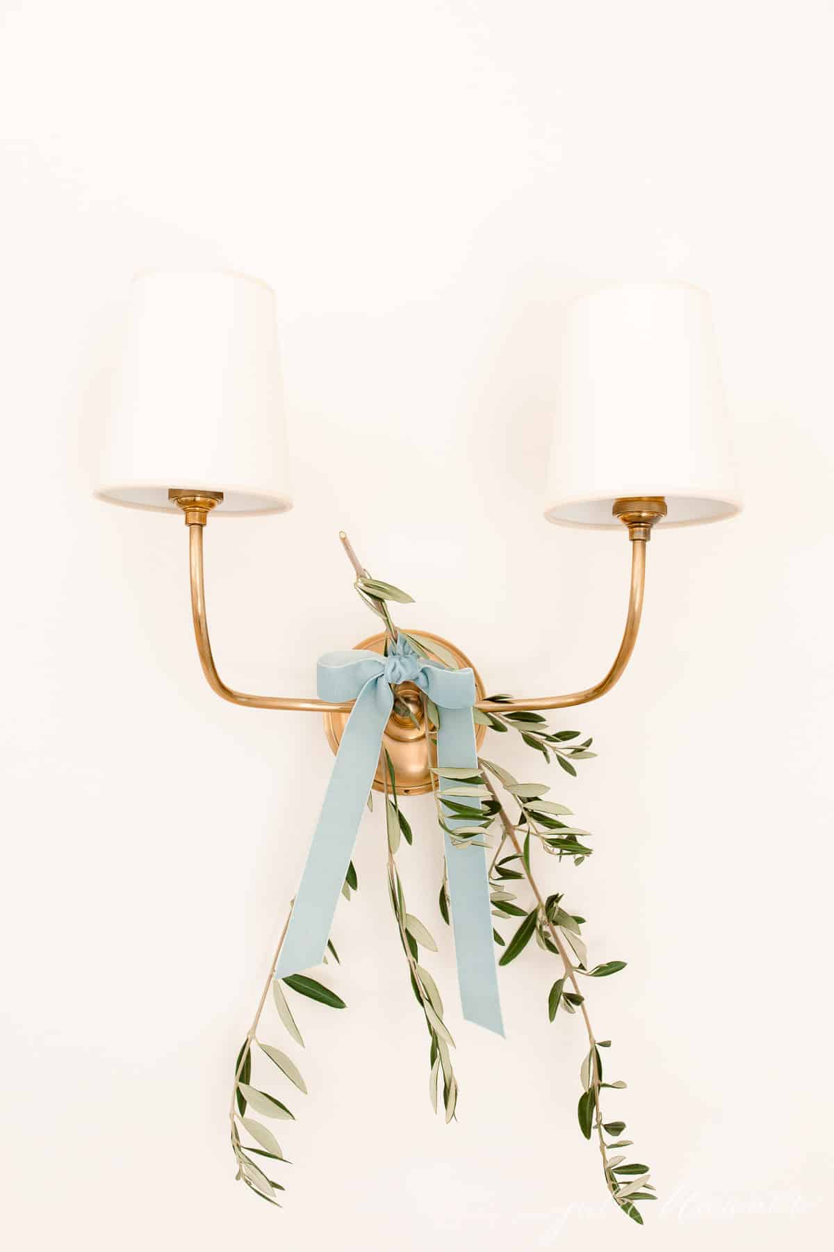 A brass two branch wall sconce with a touch of olive branch tied on with blue ribbon for a Scandinavian Christmas home tour.