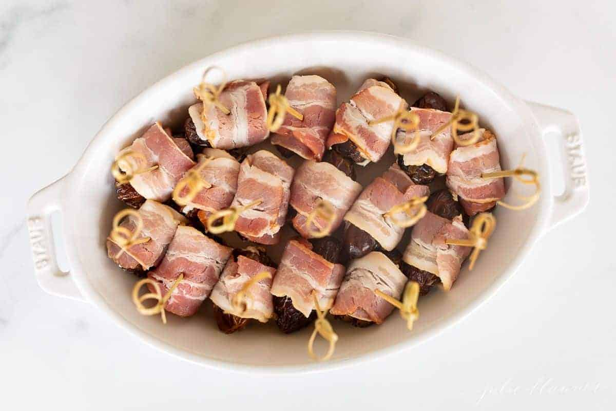 An oval baking dish filled with bacon wrapped dates before baking.