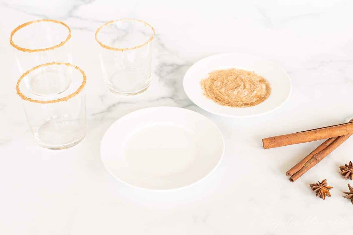 A marble surface with plates and glasses to add a sugared rim to apple cider margaritas.
