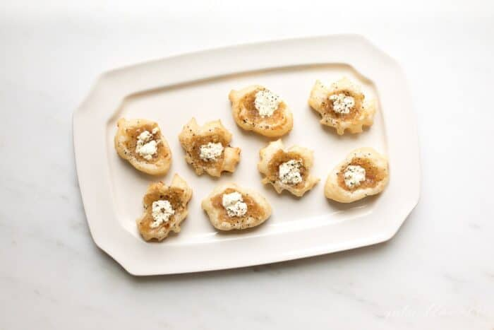 A rectangular white tray with onion tart hors d'oeuvres.