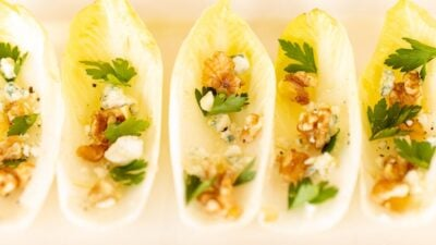 Individual endive lettuce appetizers on a white platter.
