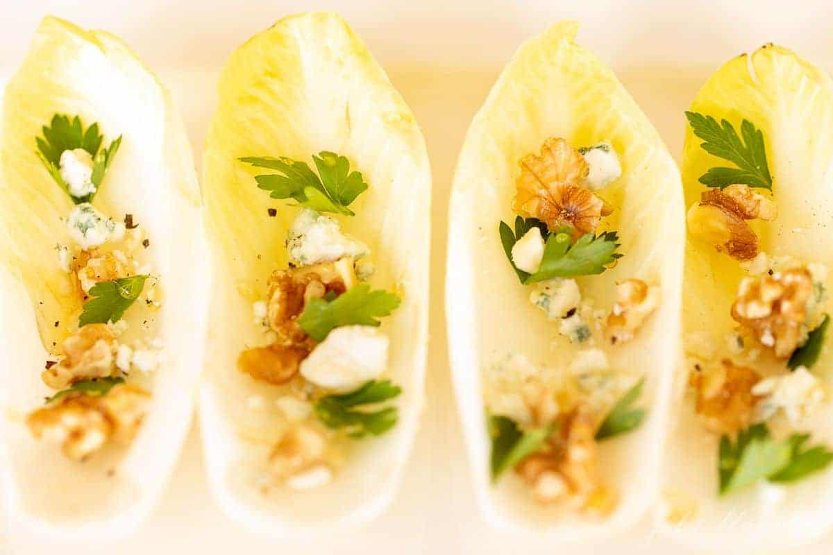 A white platter with four individual endive leafs, filled with toppings for a unique hors d'oeuvre.