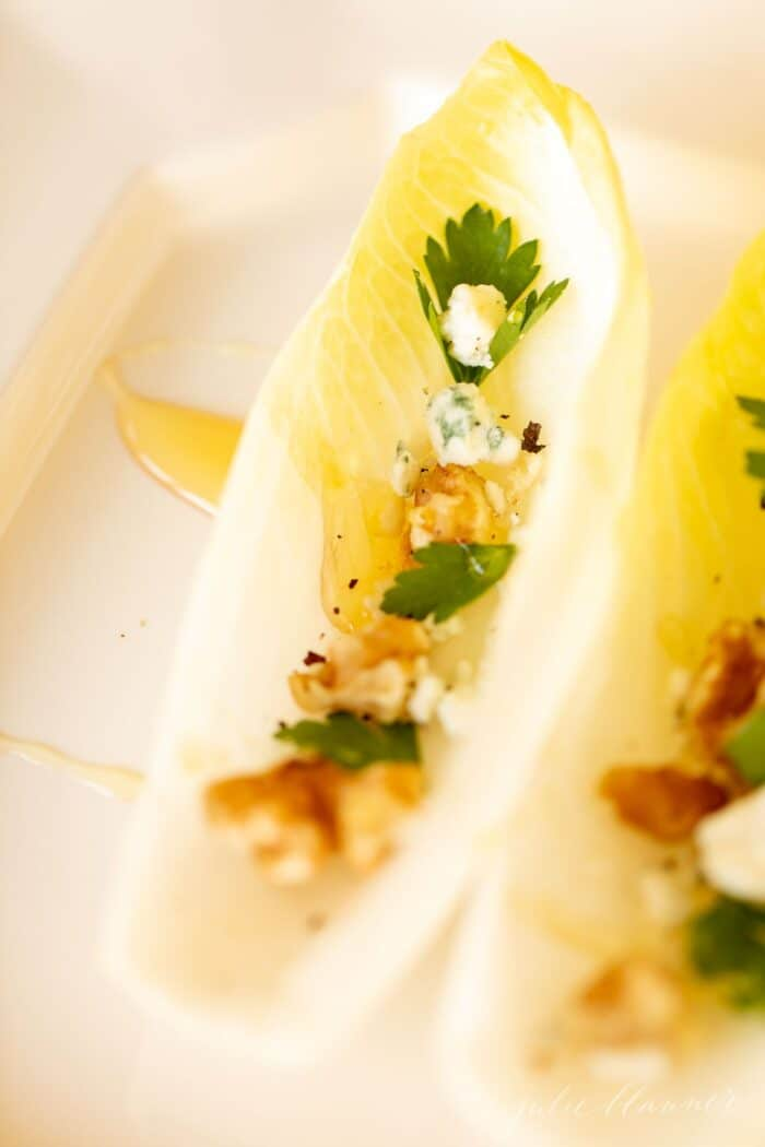 Individual endive lettuce appetizers on a white platter, drizzled with honey.