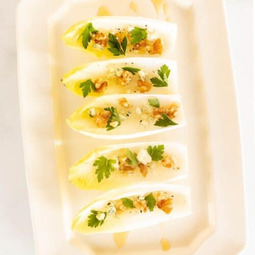 A white platter with individual endive lettuce leaves, filled with nuts, cheese and more for an endive salad appetizer.