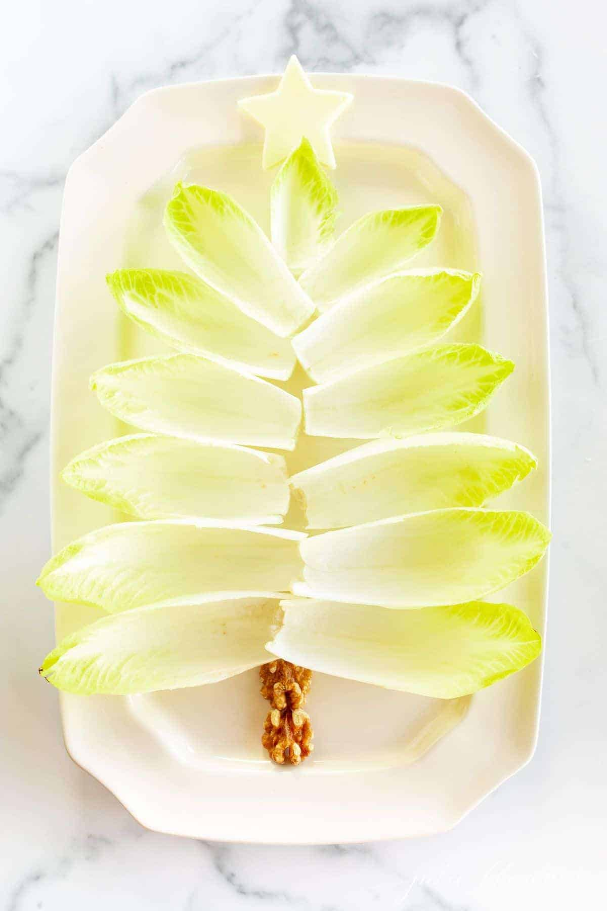 Endive lettuce leaves on a white platter formed into a Christmas tree for a holiday hors d'oeuvre.