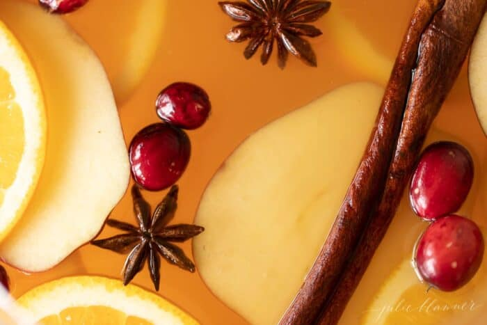A close up shot of a fall apple cider sangria recipe, with cranberries, apples and cinnamon sticks floating.