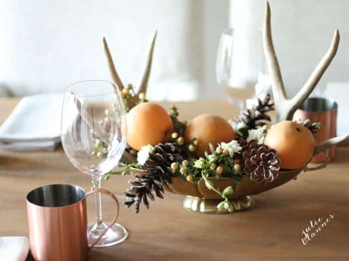 A table set for thanksgiving with a rustic centerpiece, glassware and Thanksgiving crossword puzzles at each place setting.
