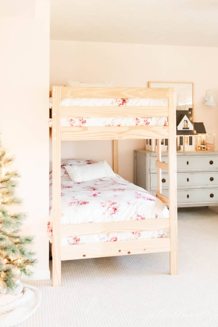 A little girls' room with bunk beds and a blue chest of drawers topped with a dollhouse decorated for Christmas.