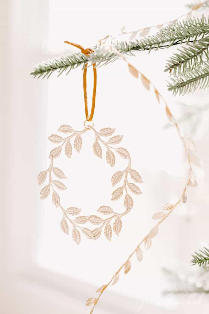 A close up of a gold wreath ornament on a Scandinavian tree.