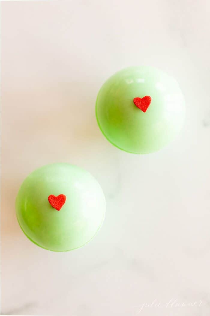 green grinch hot chocolate bombs decorated with red hearts, on a marble surface.