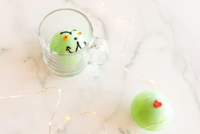 A green grinch hot chocolate bomb in a clear glass mug, a second bomb to the side on a marble surface.