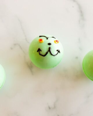 A marble surface with green grinch hot chocolate bombs.