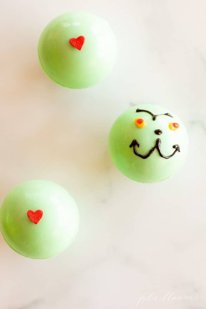 A green grinch hot chocolate bomb in a clear glass mug, more bombs to the side on a marble surface.