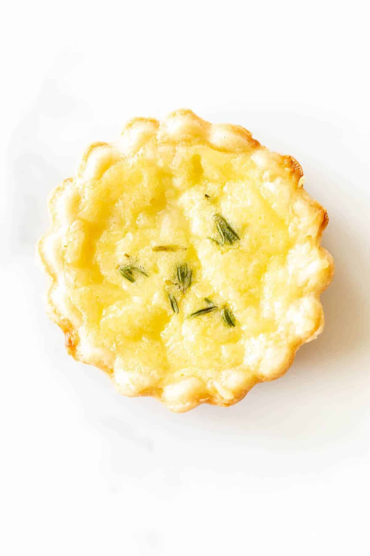 A single miniature cheese tart hors doeuvre on a white surface.