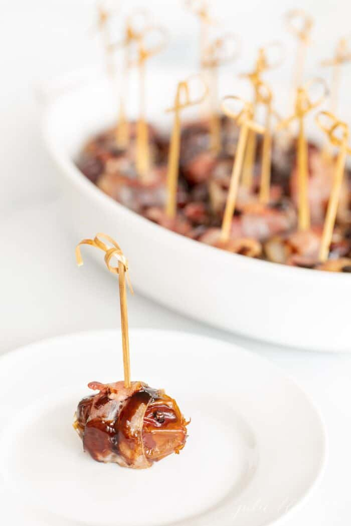 An individual stuffed date with a toothpick on a white plate, baking dish in background.
