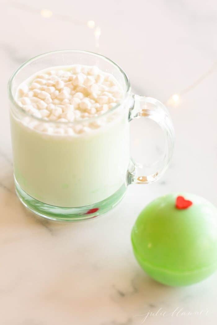A clear glass mug of grinch hot chocolate with a green grinch hot chocolate bomb to the side.
