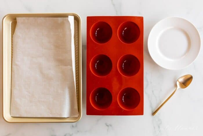A baking sheet lined with parchment paper, a silicone mold and a white plate with gold spoon, all laid out on a marble surface.
