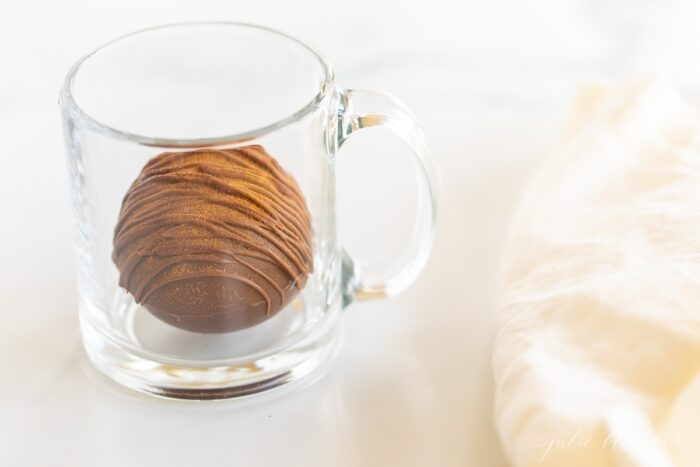 A clear mug with a spicy hot chocolate bomb inside, cinnamon stick and white linen napkin to the side.