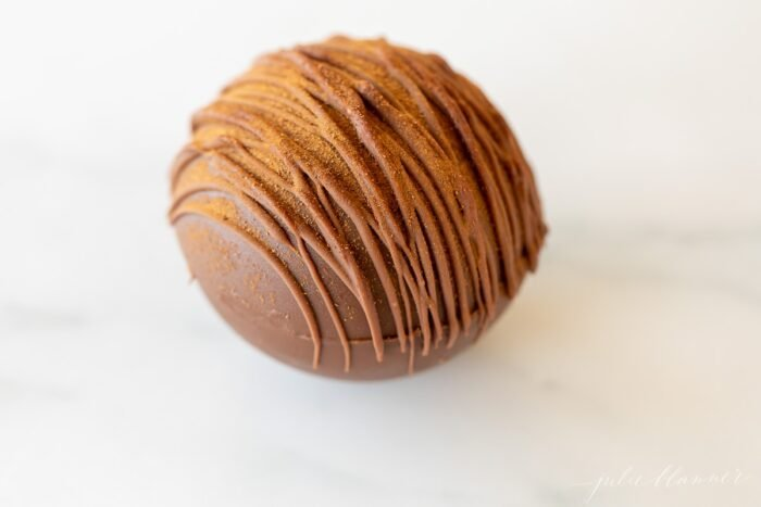 a single spicy hot chocolate bomb on a marble surface