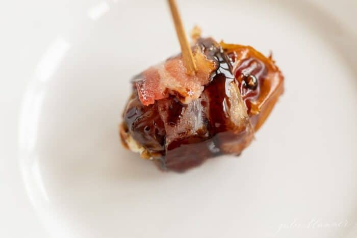 A single stuffed date on a white plate with a toothpick.