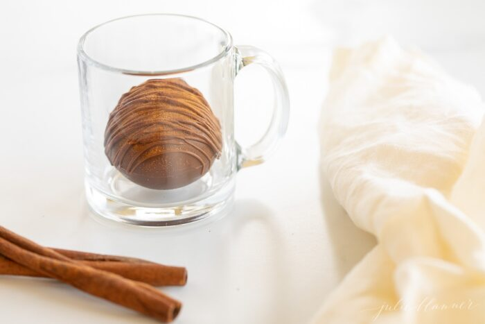A clear mug with a Mexican hot chocolate bomb inside, cinnamon stick and white linen napkin to the side.