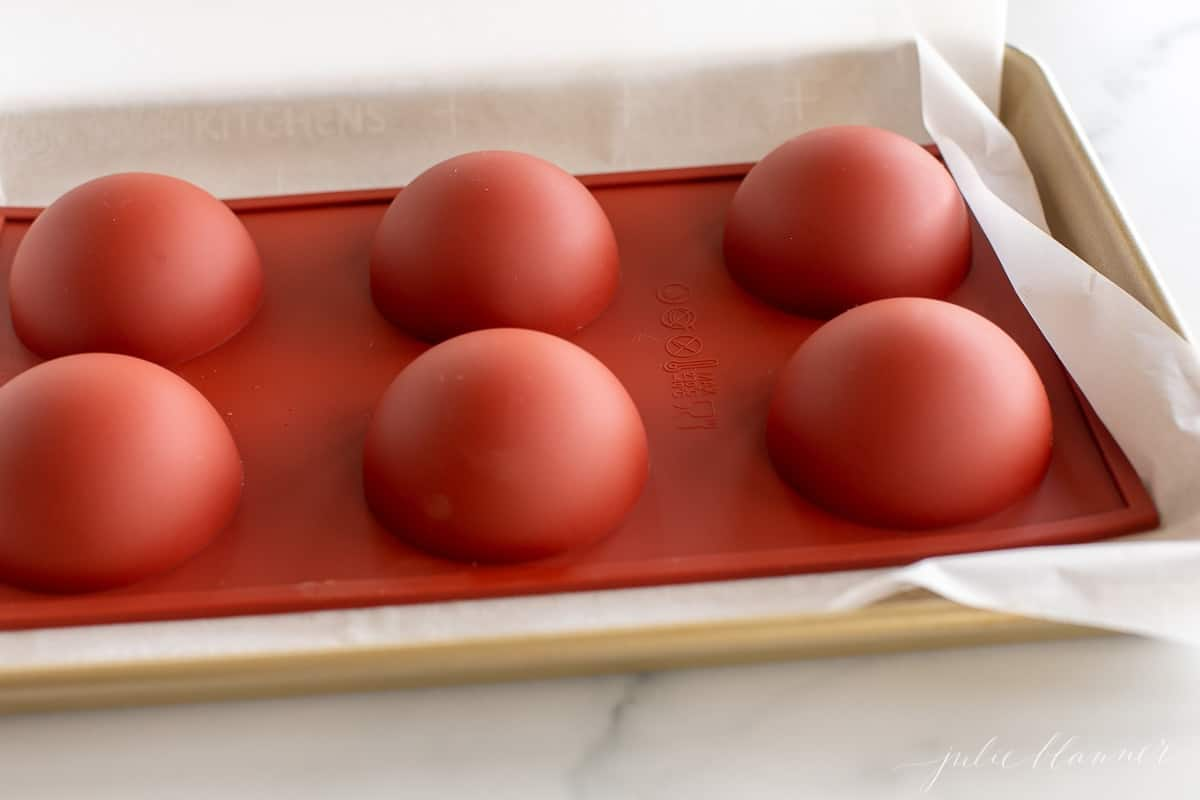 A red silicone sphere mold filled with chocolate for Mexican hot chocolate bombs, inverted on a gold baking sheet.