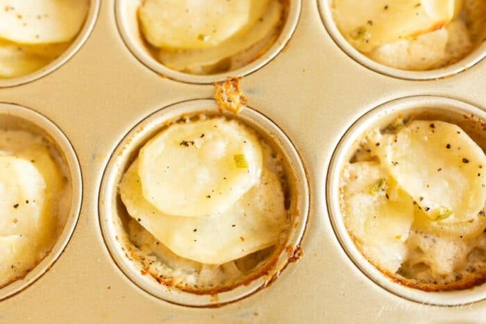 Potato gratin stacks in a gold muffin pan for individual servings.