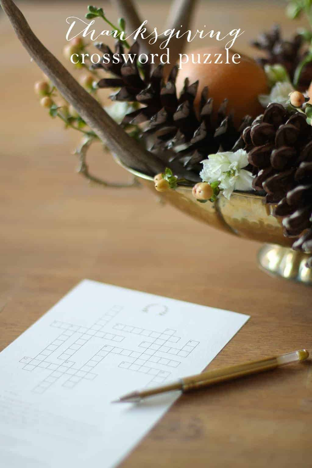 A printable Thanksgiving crossword puzzle on a wooden table with a gold centerpiece in the background.