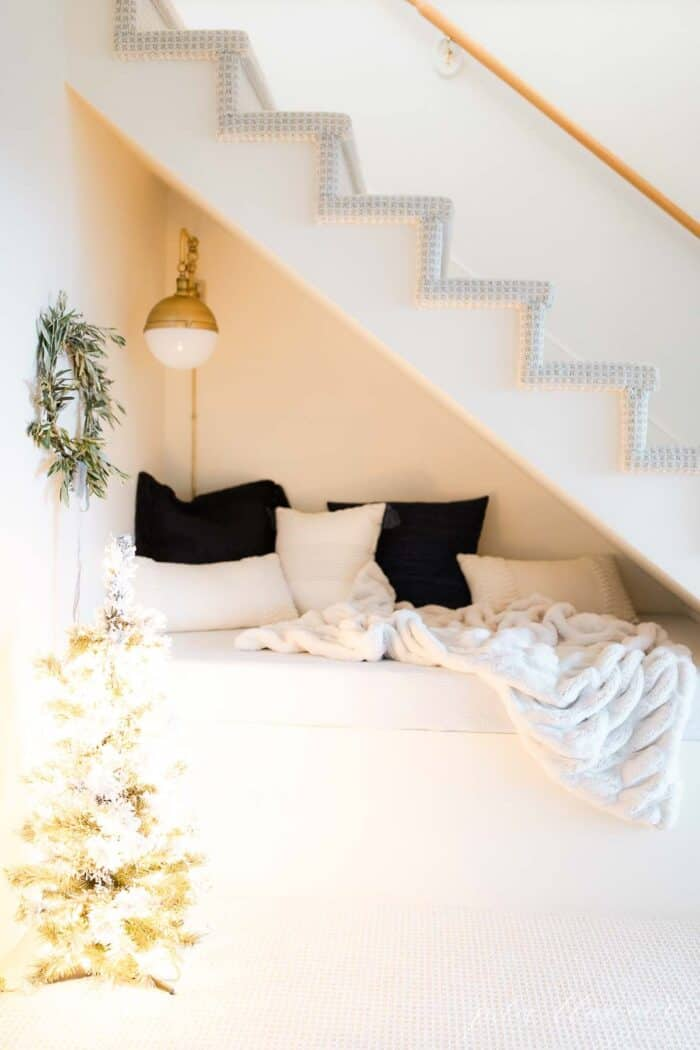 A built in nook under stairs, decorated for Scandinavian Christmas with a fresh wreath and a frosted Christmas tree.