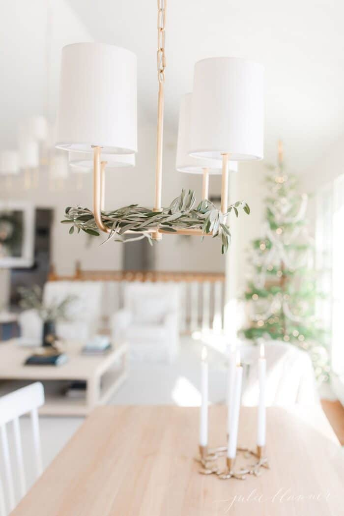 Fresh olive branches inside a brass chandelier in a Scandinavian Christmas decorated living room.