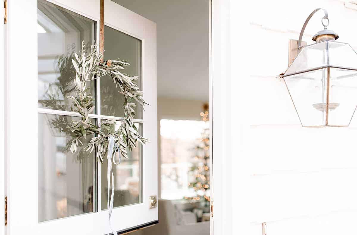 dutch door open with olive wreath peeking into a home with a scandinavian christmas tree