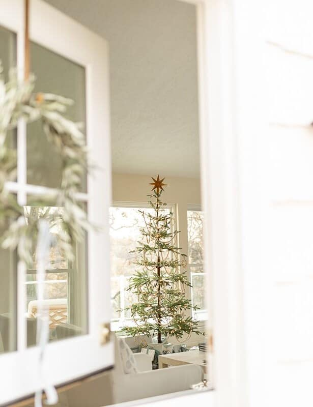 A white front porch with a natural christmas decor wreath on the dutch door.