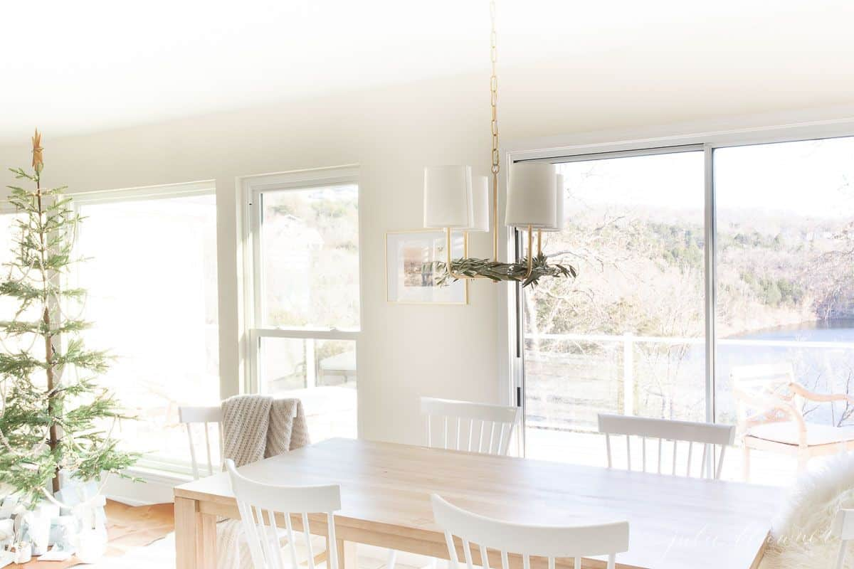 A soft wood kitchen table with white chairs and a Scandinavian tree in the background, lake view through the windows.
