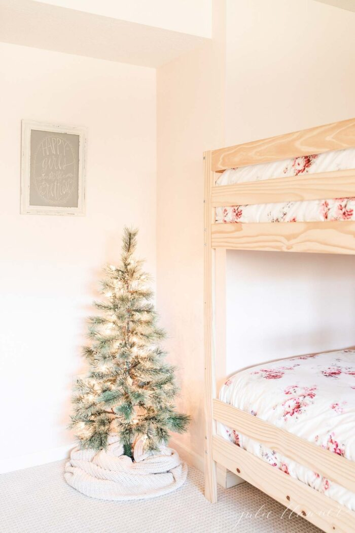 A scandinavian tree wrapped in a cable texture skirt with a bunk bed in the background.