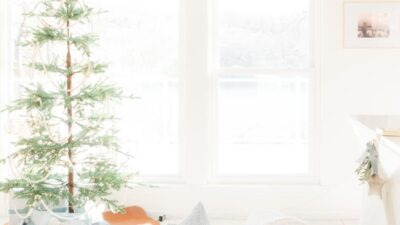 A white living room dressed for a Scandinavian Christmas with a simple Scandinavian tree.