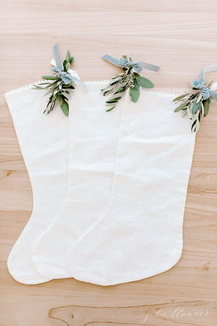 Three white linen stockings with touches of holiday greenery, laid out on a wooden surface.