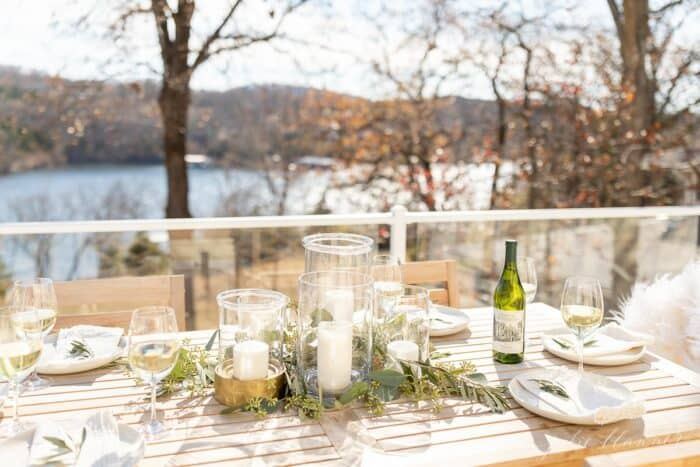 An outdoor table set for a Christmas dinner with clear glass hurricanes and greenery.